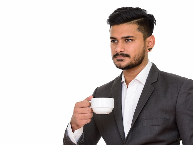 Young handsome indian businessman holding coffee cup