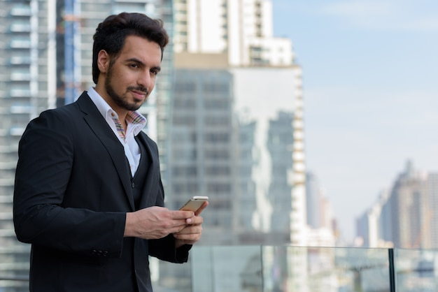Young handsome indian businessman holding mobile phone while thinking at rooftop in bangkok