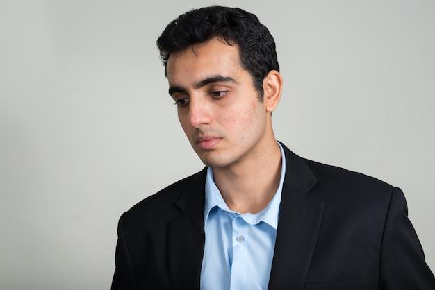 白い壁にスーツを着て若いハンサムなインドのビジネスマン