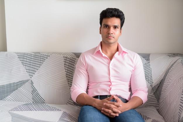 自宅のリビングルームで若いハンサムなインドのビジネスマン