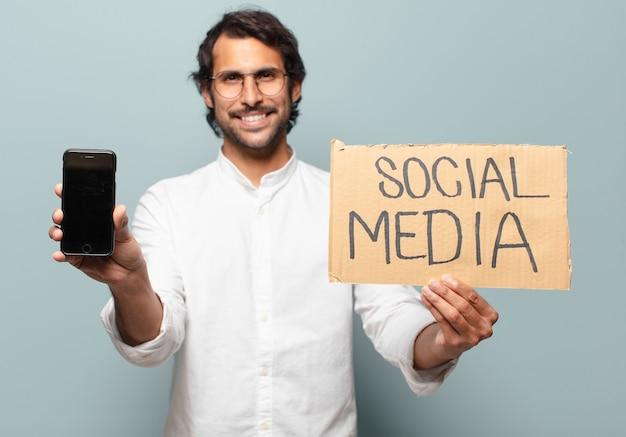 彼のセルの空の画面を表示している若いハンサムなインドのビジネスマン。ソーシャルメディアの概念