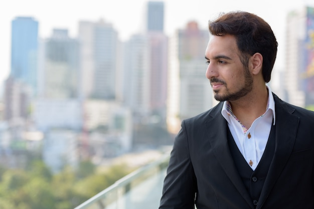 Young handsome indian businessman thinking at rooftop in bangkok