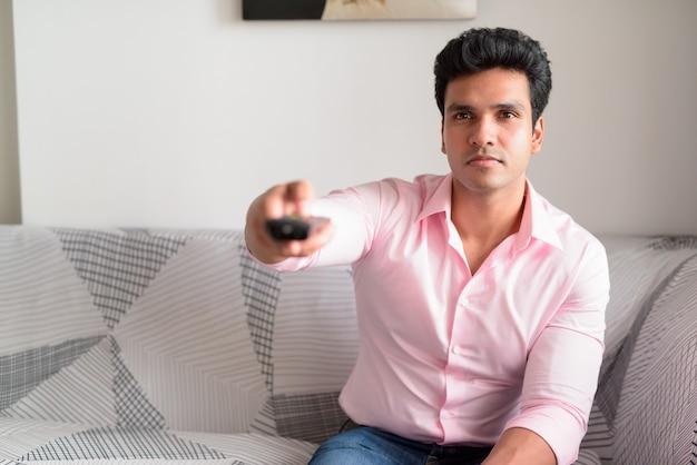 Молодой красивый индийский бизнесмен смотрит телевизор в гостиной дома