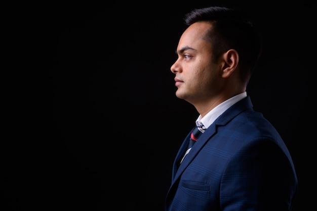 黒い壁に青いスーツを着ている若いハンサムなインドのビジネスマン