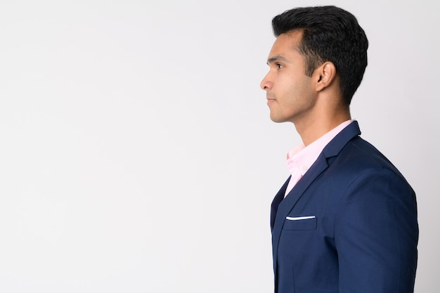 Young handsome indian businessman wearing suit against white wall
