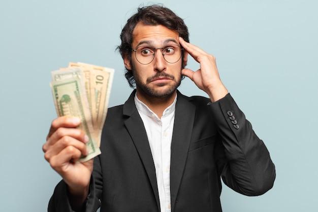 紙幣を持つ若いハンサムなインドのビジネスマン
