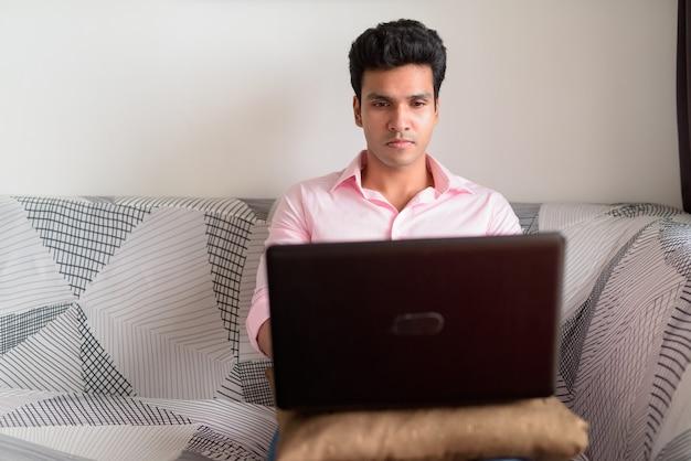 ラップトップで作業し、家にいる若いハンサムなインドのビジネスマン