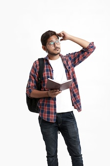 Young handsome indian college student giving thinking expression on white wall
