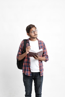Young handsome indian college student with thinking expression on white wall