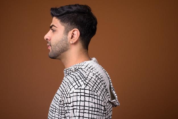 Молодой красивый индийский мужчина на коричневом фоне