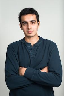 白い壁に対して若いハンサムなインド人