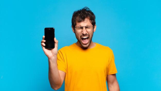 若いハンサムなインド人の怒っている表現と携帯電話を持っています