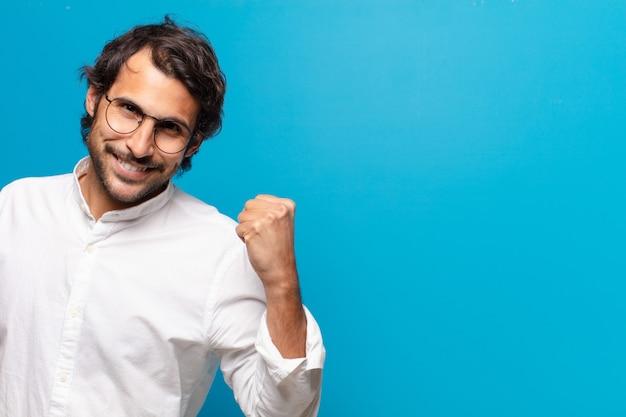 Молодой красивый индийский мужчина празднует выражение триумфа
