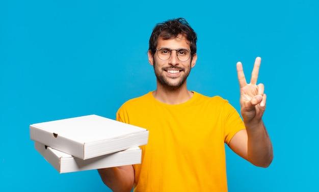 Молодой красивый индийский мужчина празднует успешную победу и держит пиццу на вынос