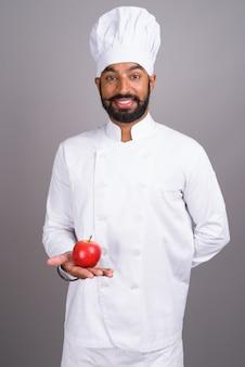 リンゴを保持している若いハンサムなインド人シェフ
