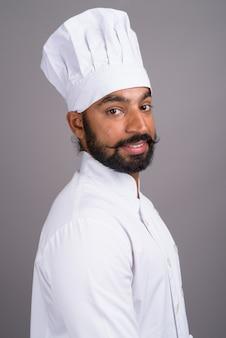 Молодой красивый индийский шеф-повар на сером фоне