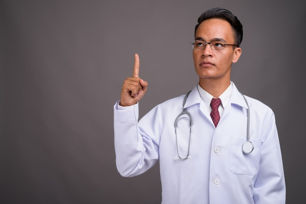 Young handsome indian man doctor against gray wall