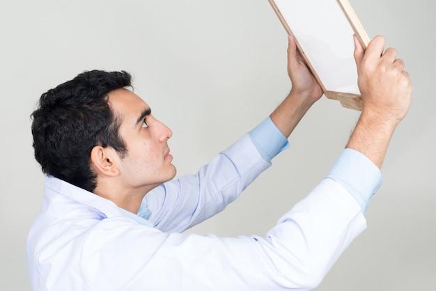 白い壁に対して若いハンサムなインド人医師