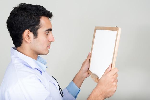 흰 벽에 젊은 잘 생긴 인도 남자 의사