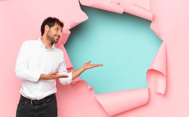 壊れた紙の穴の壁に対して疑ったり不確かな表情をしている若いハンサムなインド人