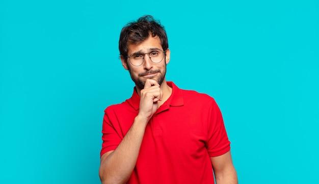 젊은 잘생긴 인도 남자 의심 또는 불확실한 표정