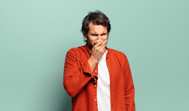 Young handsome indian man feeling disgusted, holding nose to avoid smelling a foul and unpleasant stench