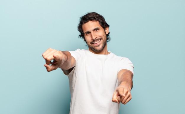 幸せで自信を持って、両手で正面を指して笑って、あなたを選んで、若いハンサムなインド人