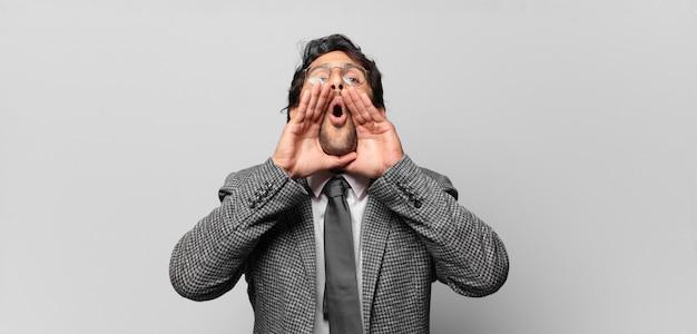 젊은 잘 생긴 인도 남자는 행복하고 흥분되고 긍정적 인 느낌, 입 옆에 손으로 큰 소리를 지르며 외칩니다. 비즈니스 개념