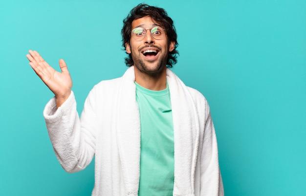 Молодой красивый индийский мужчина чувствует себя счастливым, удивленным и веселым, улыбаясь с позитивным настроем