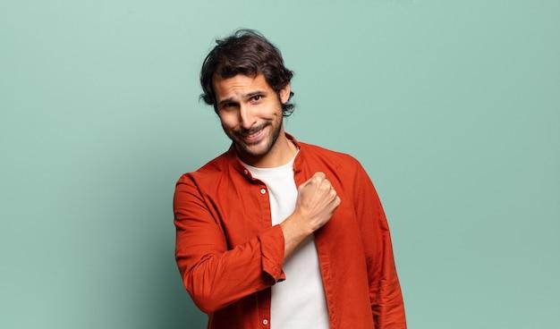 Молодой красивый индийский мужчина чувствует себя счастливым