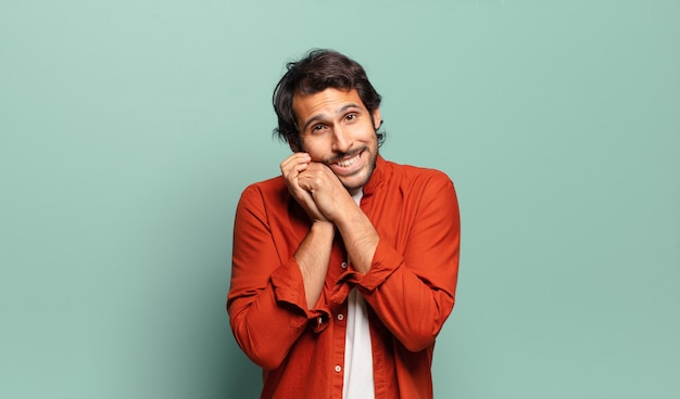 Young handsome indian man feeling in love and looking cute, adorable and happy, smiling romantically with hands next to face