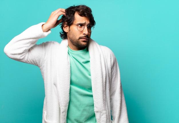 젊은 잘 생긴 인도 남자는 어리둥절하고 혼란스러워서 머리를 긁적이며 옆을 바라보고 목욕 가운을 입고 있습니다.