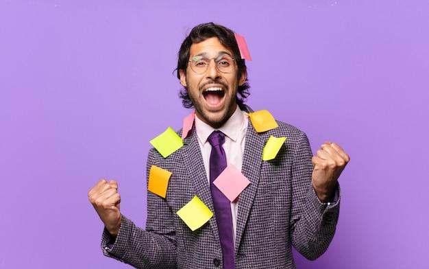 젊은 잘 생긴 인도 남자는 충격을 받고, 흥분하고, 행복하고, 웃음과 성공을 축하하고, 와우!. 유머러스 한 비즈니스 개념