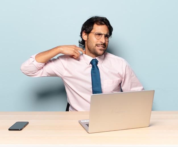 Молодой красавец-индеец чувствует стресс, тревогу, усталость и разочарование, тянет рубашку за шею и выглядит разочарованным из-за проблемы. концепция бизнеса и фрилансера