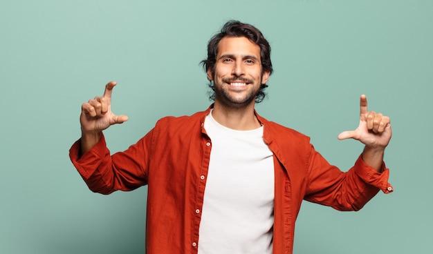 若いハンサムなインド人は、両手で自分の笑顔をフレーミングまたは概説し、前向きで幸せそうな、ウェルネスコンセプト