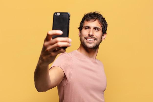 젊은 잘생긴 인도 남자. 행복하고 놀란 표정 스마트폰 개념