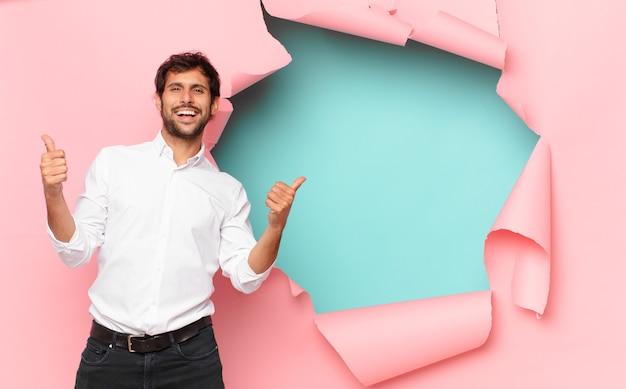 壊れた紙の穴の背景に対して若いハンサムなインド人幸せな表現