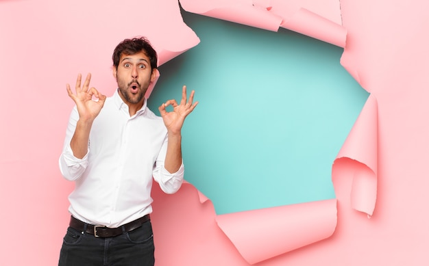 壊れた紙の穴に対して若いハンサムなインド人幸せな表現