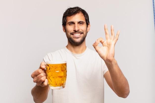 若いハンサムなインド人の幸せな表現とビールを持っています