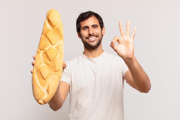 Молодой красивый индийский мужчина счастливое выражение и держит хлеб