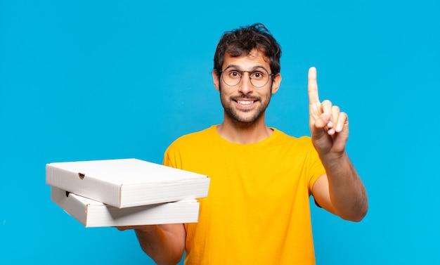 Молодой красивый индийский мужчина счастливым выражением лица и держит пиццу на вынос