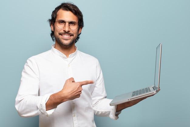 노트북을 들고 젊은 잘 생긴 인도 남자. 비즈니스 또는 소셜 미디어 개념