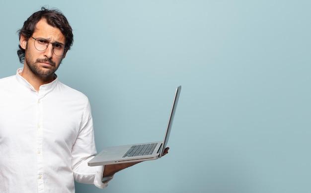 노트북을 들고 젊은 잘생긴 인도 남자. 비즈니스 또는 소셜 미디어 개념