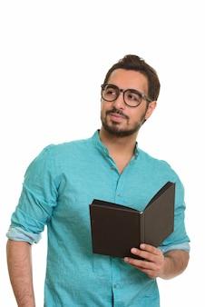 Молодой красивый индийский мужчина держит книгу, думая