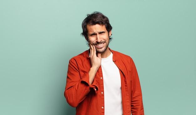 Молодой красивый индийский мужчина держится за щеку и страдает от болезненной зубной боли, чувствует себя плохо, несчастно и несчастно, ищет дантиста
