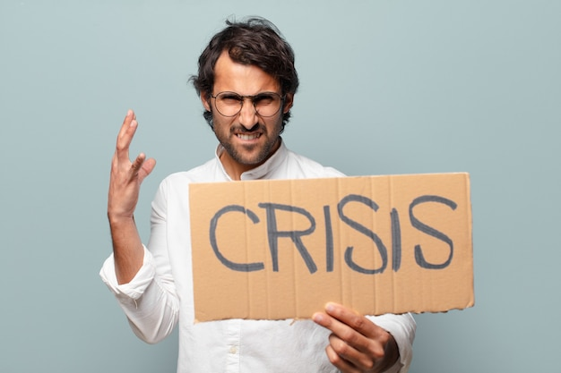 Young handsome indian man holding crisis board