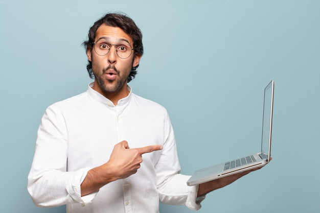 Young handsome indian man holding a laptop