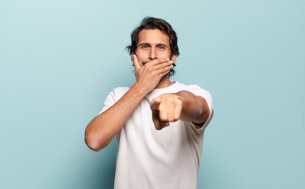 젊은 잘 생긴 인도 남자가 당신을 비웃고, 가리키며 조롱하거나 조롱합니다.