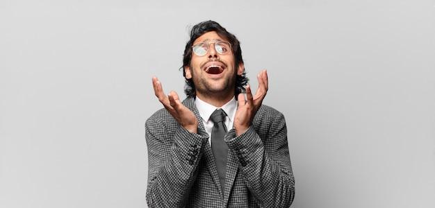 절망과 좌절, 스트레스, 불행하고 짜증이 나서 소리 지르고 비명을 지르는 젊은 잘 생긴 인도 남자. 비즈니스 개념