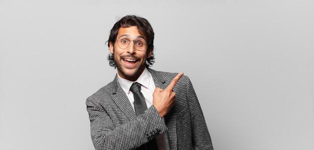 スペースをコピーするために横と上を指して興奮して驚いたように見える若いハンサムなインド人。ビジネスコンセプト